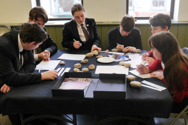 Pupils writing names on the stones
