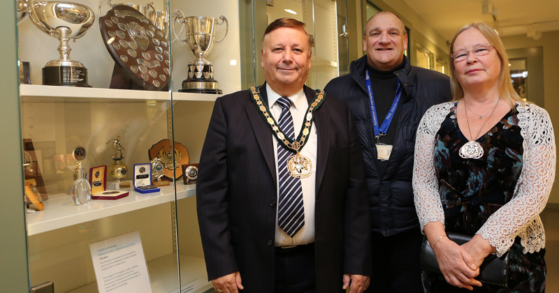 Chairman Richard Bassett with wife Sue and Cllr Nigel Bedford by the trophy cabinet