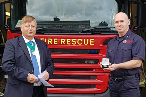 Bradley Reynolds receiving the Community Service medal for Essex Fire and Rescue from Cllr Richard Bassett