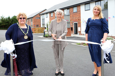 The chaiman and Cllr Holly Whitbread standing with Shirley Hawkins as she cuts a white ribbon outside the new development.